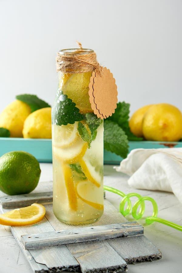 limonade de boisson non alcoolisée dans une bouteille en verre et des citrons frais mûrs photographie stock