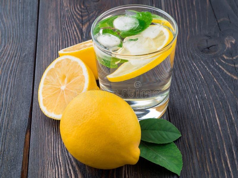 Limonade in einem Glas, eine Zitrone halb, frische Blätter auf dunkelbraunem wo stockbild