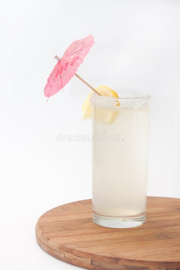 Limonade in einem Glas mit einem Regenschirm und einer Zitrone lizenzfreie stockfotografie