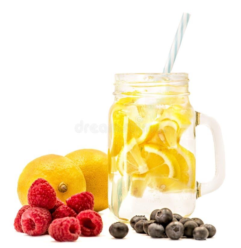 Limonade in einem Weckglas mit einem Trinkhalm verziert mit Scheiben der Wassermelone, der Himbeeren und der Blaubeeren lokalisie stockfoto