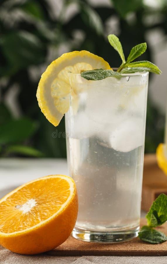 Limonade en bon état d'agrume avec des glaçons dans la tasse en verre à côté de la carafe de vintage Boisson Limoncello d'été photos libres de droits