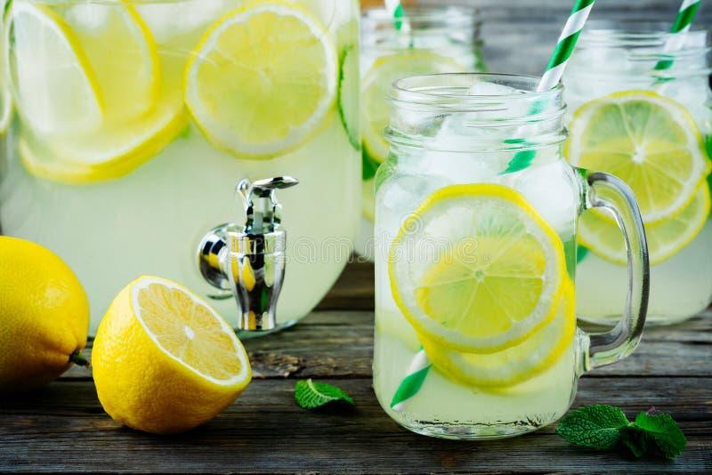 Limonade faite maison avec la menthe, la glace, et les tranches fraîches de citron dans le pot de maçon image stock