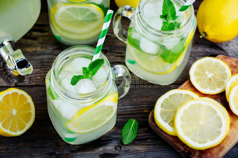 Limonade faite maison avec la menthe, la glace, et les tranches fraîches de citron dans le pot de maçon photo stock