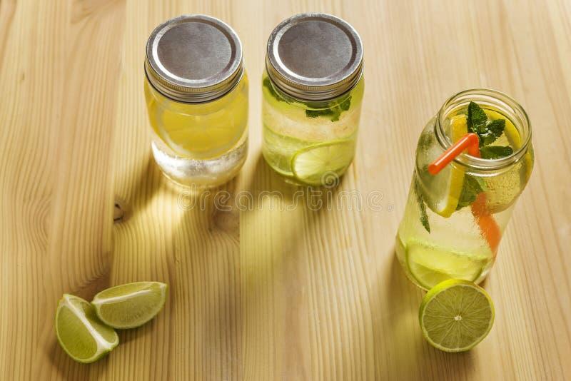Limonades door zonlicht op houten lijst worden verlicht die stock foto's