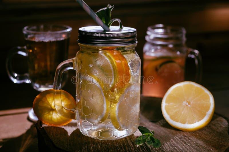 Limonata arancio casalinga del lenon della calce sui precedenti rustici scuri fotografie stock libere da diritti