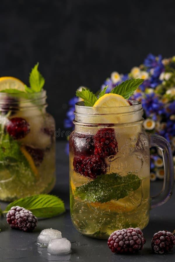Limonata casalinga con il limone, la mora e la menta in vetro contro un fondo scuro, foto verticale fotografia stock