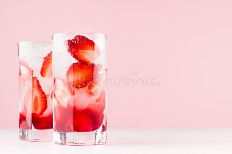 Limonata casalinga della fragola fredda di estate con le fette mature bacca, ghiaccio su fondo rosa-chiaro molle, tavola di legno immagini stock libere da diritti