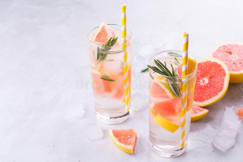 Limonata del pompelmo Due vetri della bevanda di rinfresco, dell'acqua con il pompelmo, dei rami dei rosmarini e del ghiaccio immagini stock libere da diritti