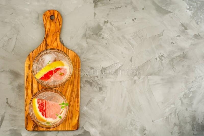 Limonata del pompelmo Due vetri della disintossicazione bevono, l'acqua con il pompelmo, rami dei rosmarini e ghiaccio Concetto d fotografie stock