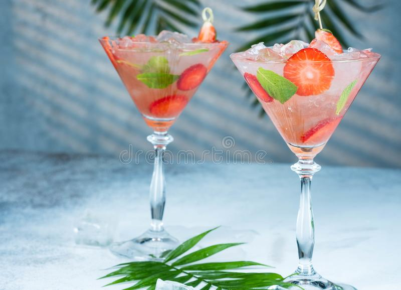 Limonata della fragola o cocktail dell'alcoolizzato con le foglie della soda e di menta dello sciroppo del ghiaccio sulla tavola  immagini stock