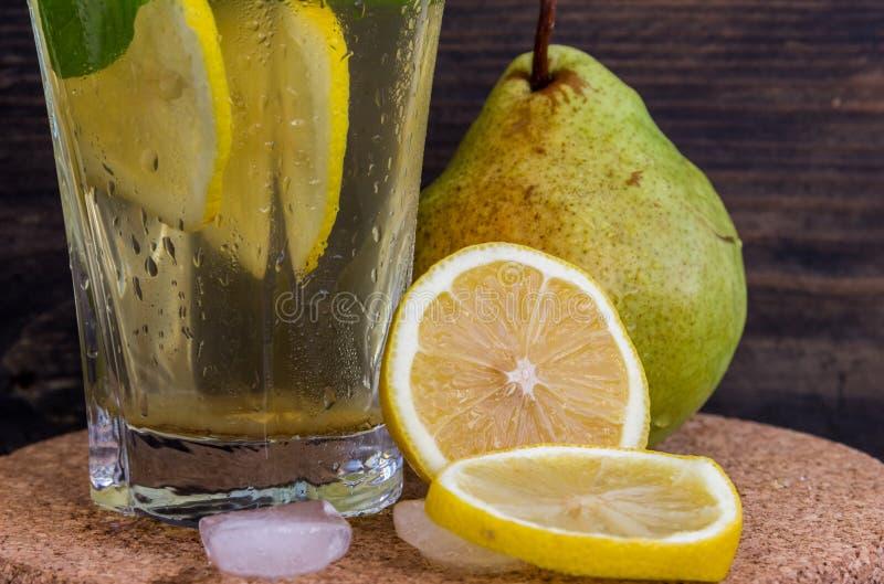 Limonata delle pere mature con il limone e la menta su un fondo scuro immagine stock
