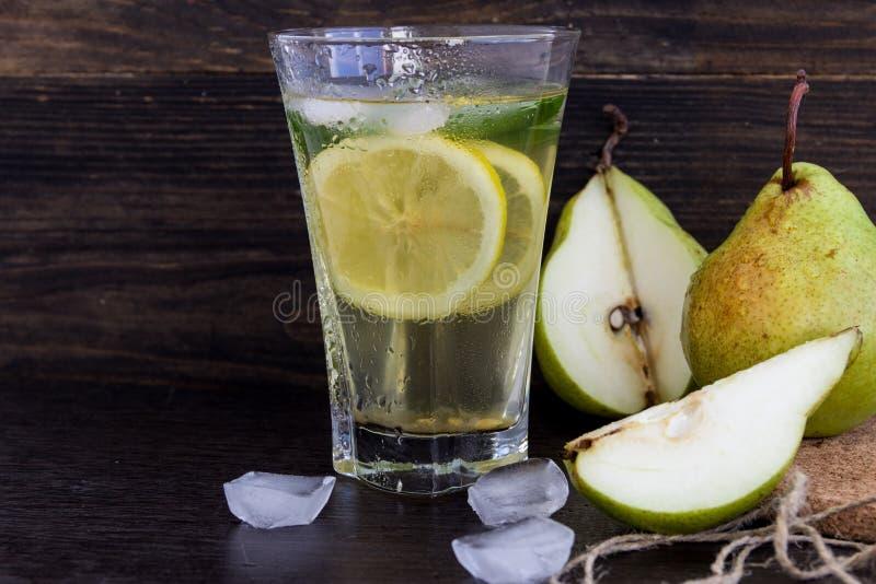Limonata delle pere mature con il limone e la menta su un fondo scuro immagine stock libera da diritti