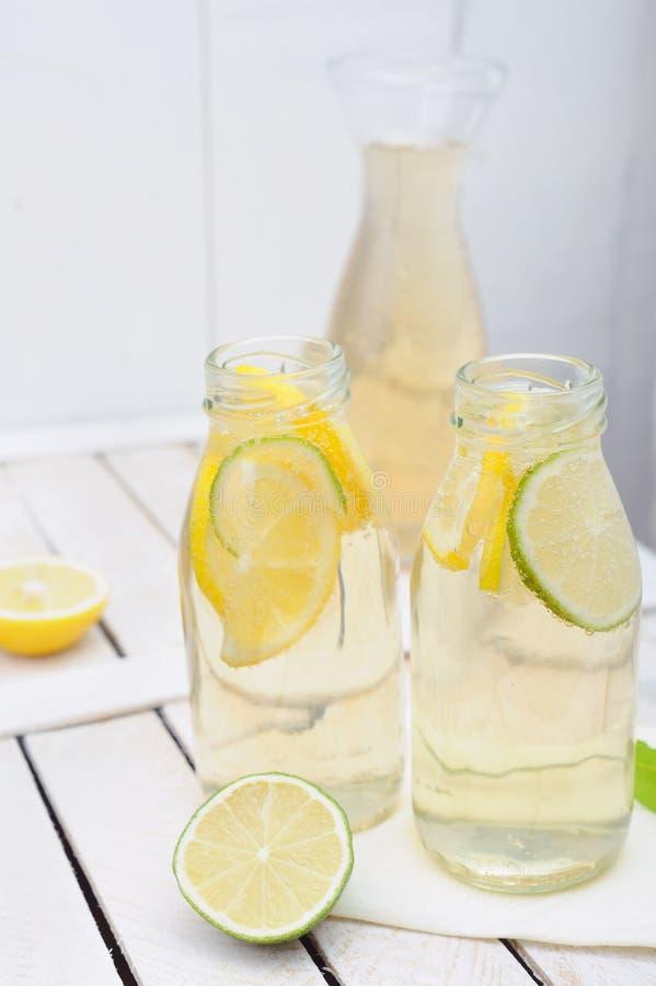 Limonata nella brocca e nei vetri con i limoni e la limetta sulla tavola bianca fotografia stock libera da diritti