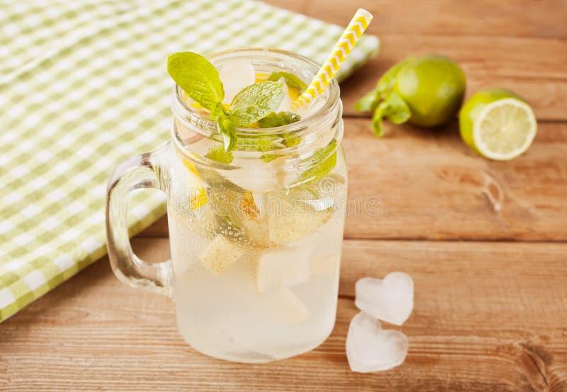 Limonata o cocktail di mojito con il limone e menta, bevanda di rinfresco fredda o bevanda sulla tavola di legno immagine stock