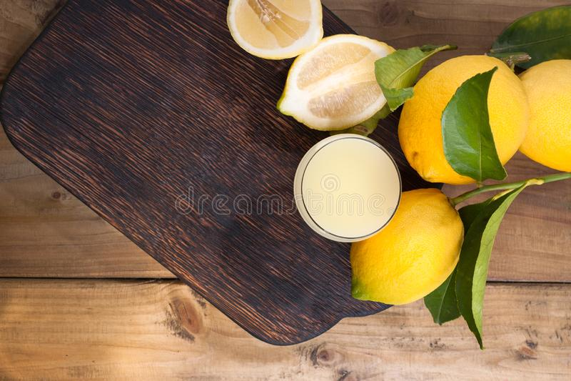 Limoncello和柠檬在一个木板 意大利的传统酒精饮料,从柑橘 新鲜水果和饮料 自由 免版税库存图片
