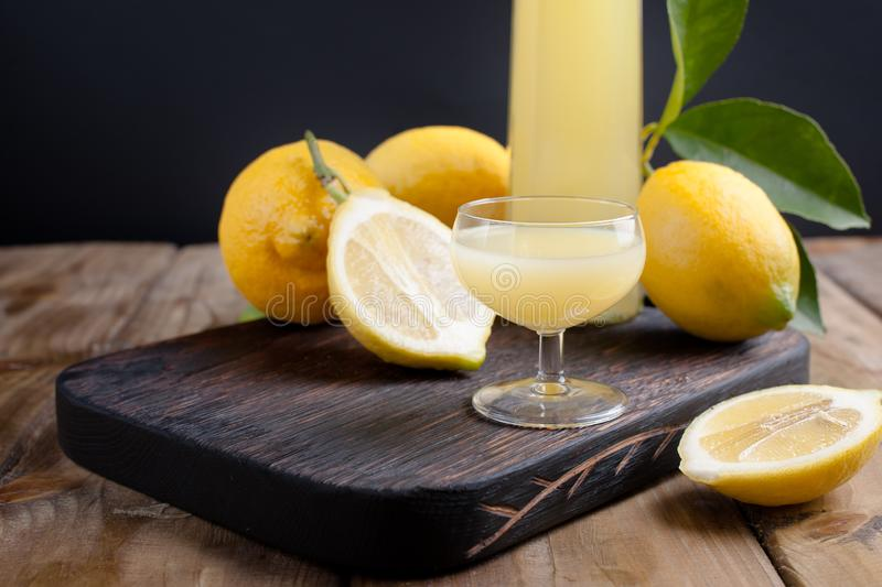 Limoncello in a bottle and a small shot with liquor. The traditional alcoholic beverage of Italy, from citrus. Fresh fruits and. Drinks. Free space for tex royalty free stock photos
