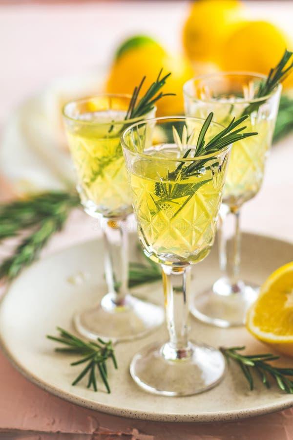 Limoncello de liqueur avec des morceaux d'herbe de citron et de romarin image libre de droits