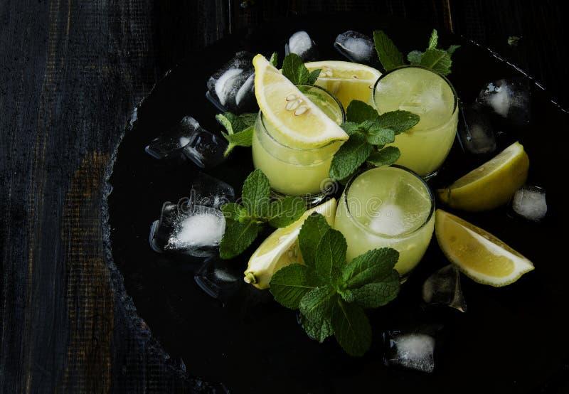 Limoncello, de traditionele likeur van Iralian met citroenen op de uitstekende lijst stock afbeelding