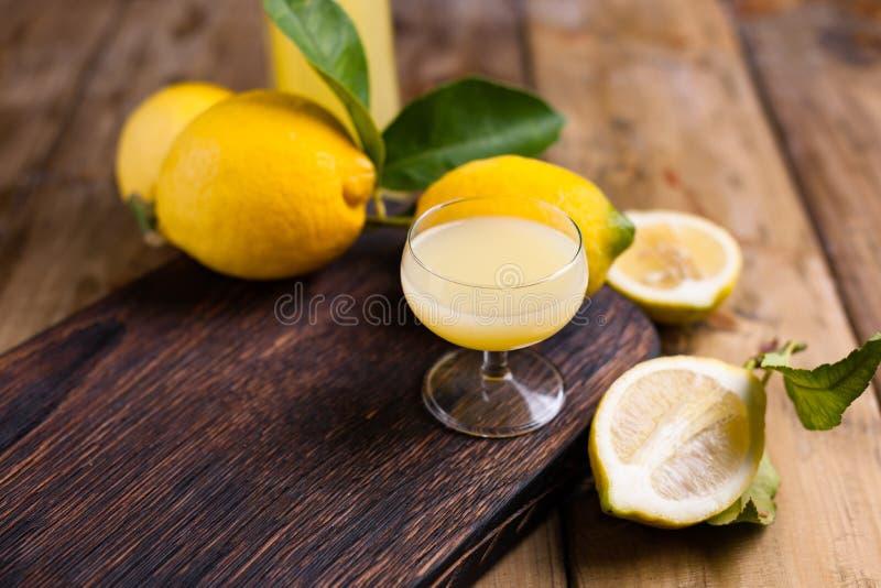 Limoncello e limoni su un bordo di legno L'alcool tradizionale immagine stock libera da diritti