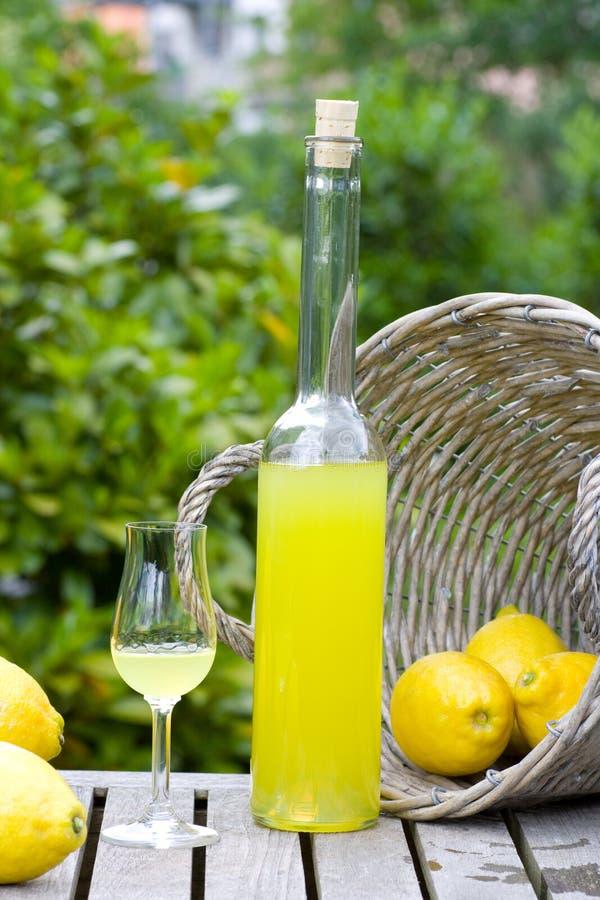 Limoncello et panier avec des citrons images stock
