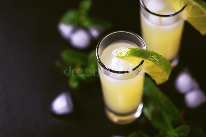 Limoncello italiano do licor do cal do limão com gelo e hortelã fotografia de stock royalty free