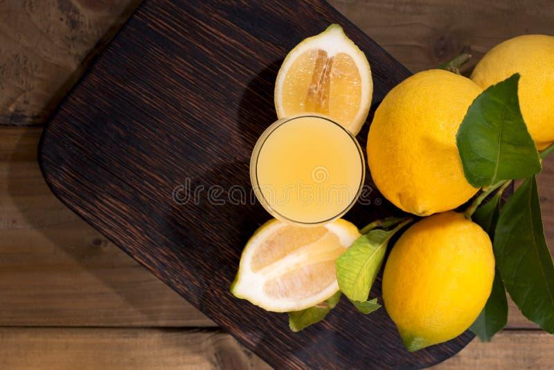 Limoncello w ?wie?ych cytrus owoc z zielonymi li??mi i szkle Tradycyjny W?oski cytryna ajerkoniak Alkohol na zmroku drewnianym fotografia stock