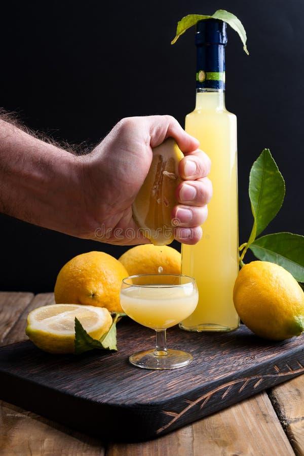 Limoncello y el limón a disposición, exprime el jugo en un vidrio La bebida alcohólica tradicional de Italia, de la fruta cítrica foto de archivo libre de regalías