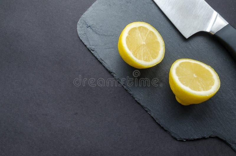 Limone affettato accanto al coltello sopra superficie nera immagine stock