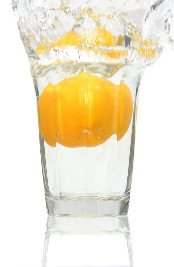 Limone che cade in un bicchiere d'acqua immagini stock libere da diritti