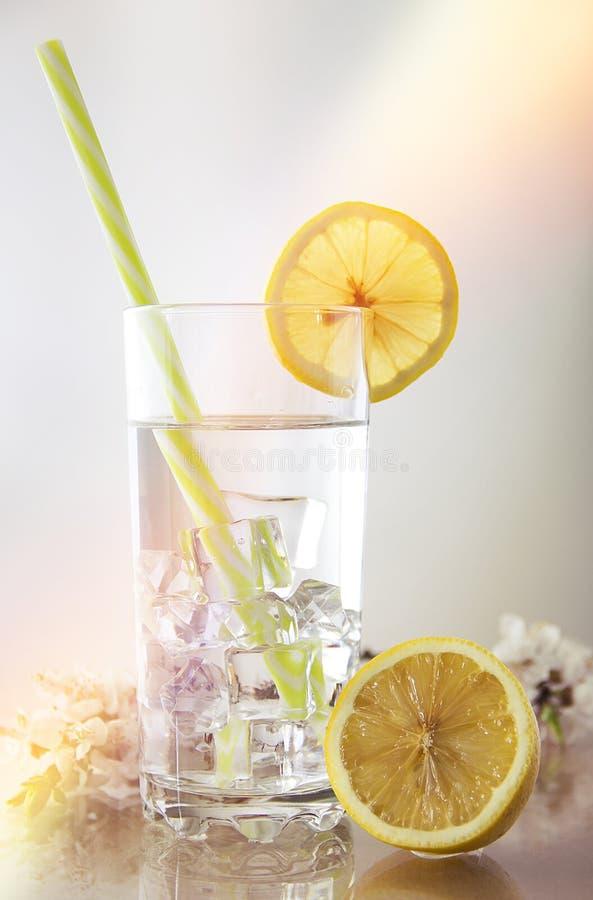 Limone del bicchiere d'acqua Un vetro della bevanda di raffreddamento con una paglia Vetro sulla tavola di vetro fotografia stock libera da diritti