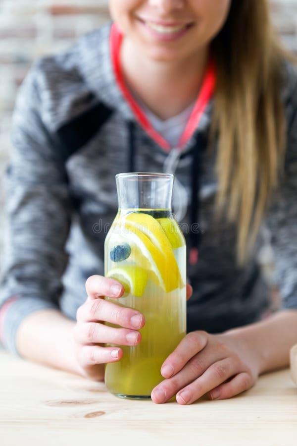 Limone della bella giovane donna e succo beventi delle bacche nella cucina a casa fotografia stock