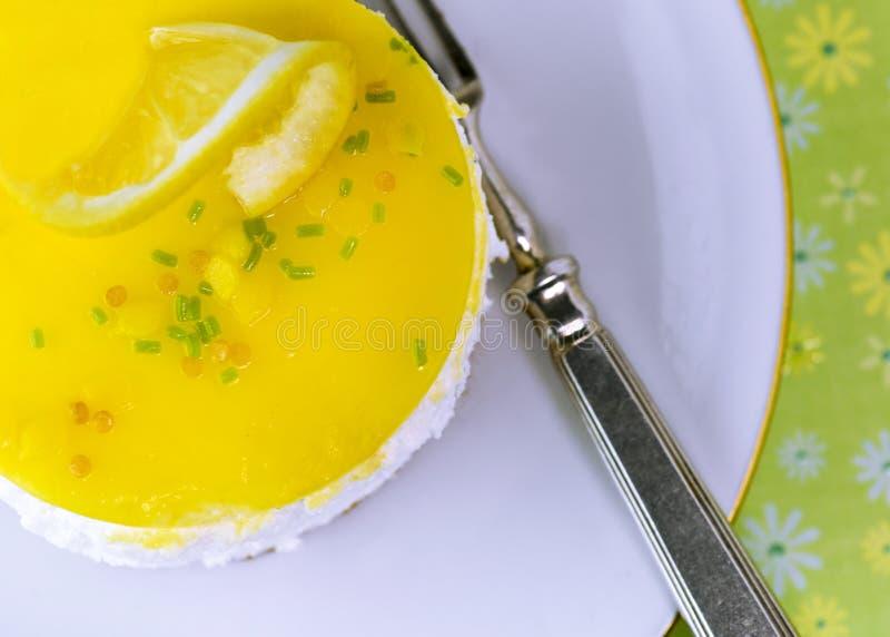 Limone della torta di formaggio su un piatto bianco con un fondo verde colorato immagine stock libera da diritti