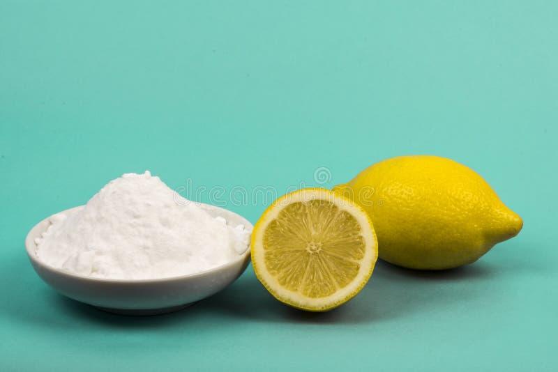 Limone e bicarbonato di sodio in un piattino isolato in blu al neon fotografia stock