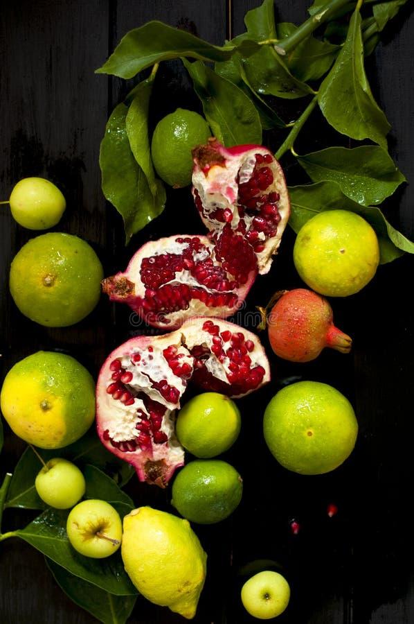 Limone su un ramo e sulle calce granata tagliata Su un fondo nero Foto scura Gocce di acqua Frutta bagnata fotografie stock