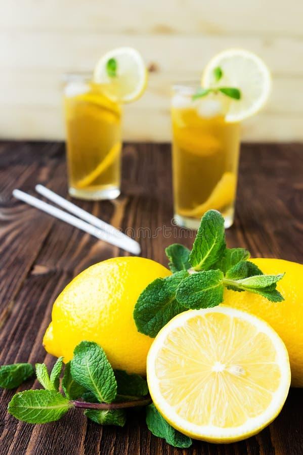 Limones con la menta y dos vidrios de té de hielo foto de archivo
