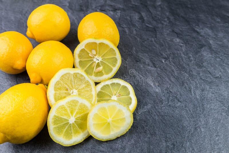 Limones enteros y cortado en un worktop de la cocina foto de archivo