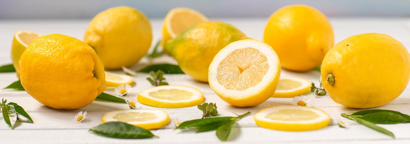 Limones enteros y extensión cortada en el tablero, adornado con las hierbas y las margaritas fotografía de archivo libre de regalías