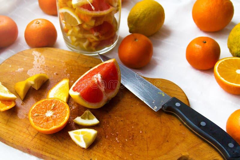 Limones, naranjas, mandarinas, pomelo, corte en rebanadas y doblado en un tarro fotos de archivo libres de regalías