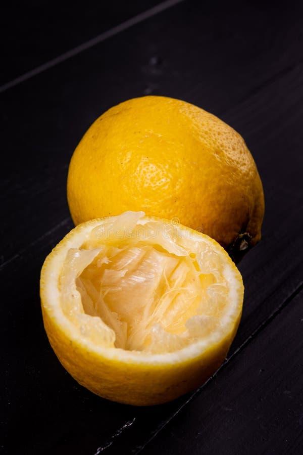 Limones usados para la limonada en la tabla negra imagen de archivo