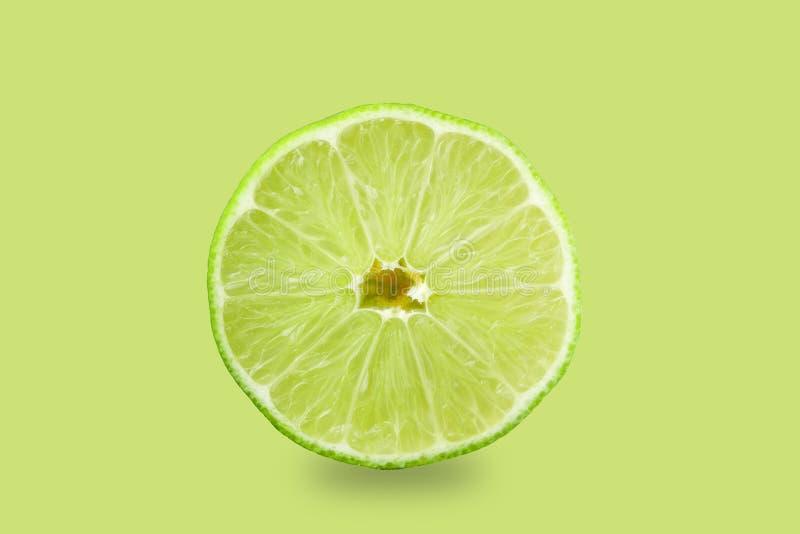 Limones y cal Abone una rebanada con cal de cal en un fondo verde, aislante imagen de archivo