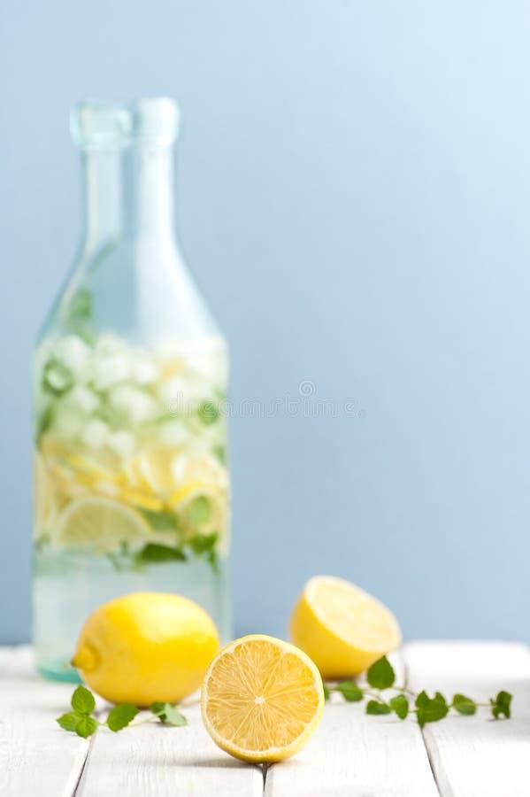 Limones y hojas de menta maduros contra la perspectiva de una botella o imagen de archivo libre de regalías