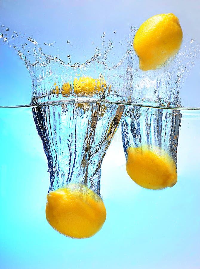 Limoni che cadono nella spremuta fotografie stock