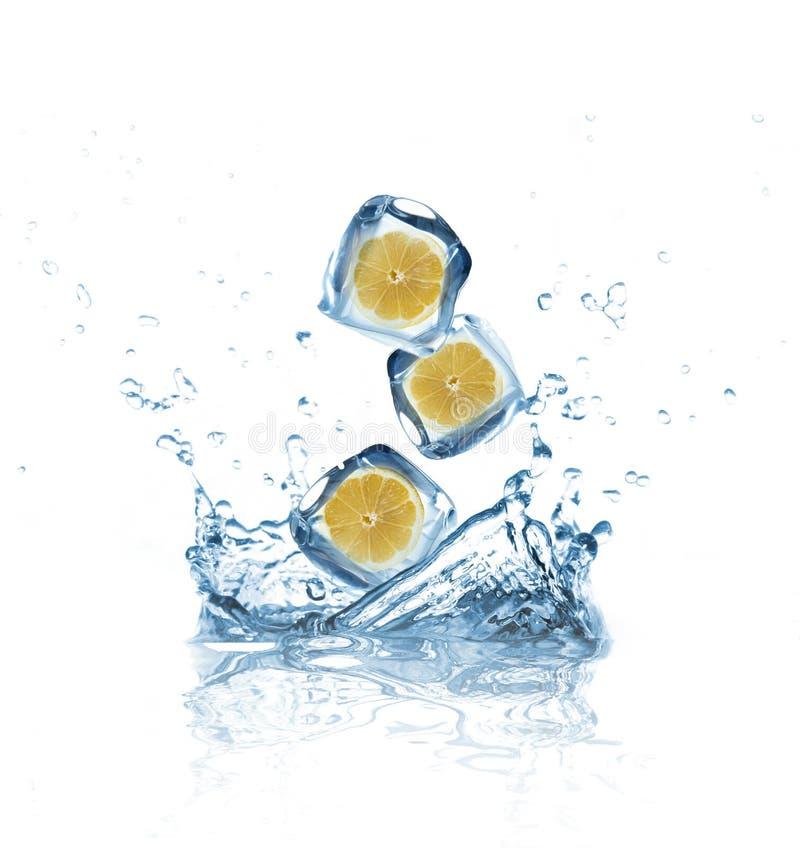 Limoni con i cubi di ghiaccio che spruzzano nell'acqua fotografia stock libera da diritti