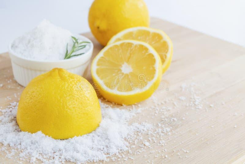 Limoni e sale marino - Trattamento di bellezza con cosmetici organici con ingredienti di limone sul legno e sullo sfondo di rosma fotografie stock