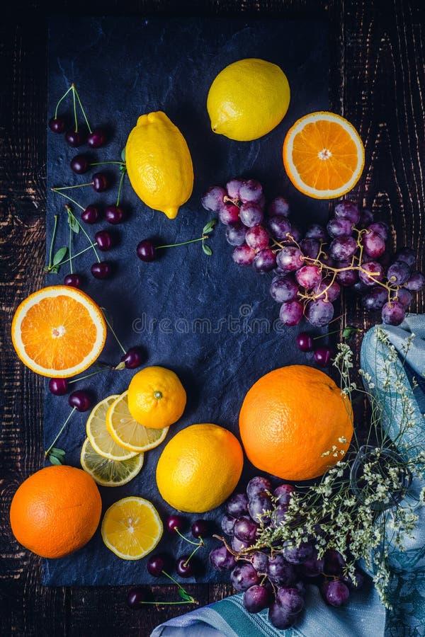 Limoni ed arance sul ciano verticale del fondo fotografie stock libere da diritti