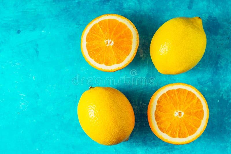 Limoni ed arance sulla vista superiore del ciano fondo immagini stock