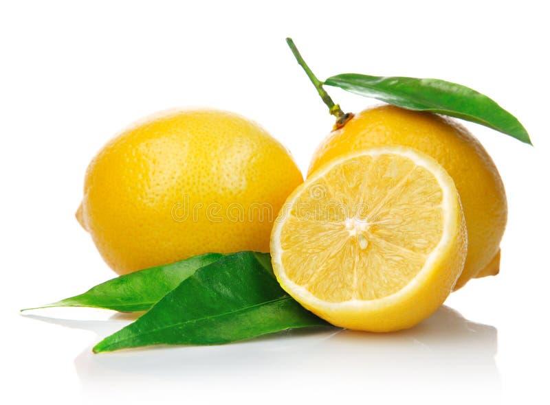 Limoni freschi con i fogli di verde e del taglio fotografie stock