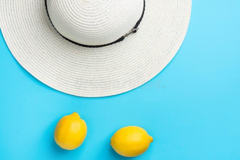 Limoni gialli organici maturi della paglia delle donne del cappello bianco della spiaggia sul fondo blu della menta Modo di diver immagine stock libera da diritti