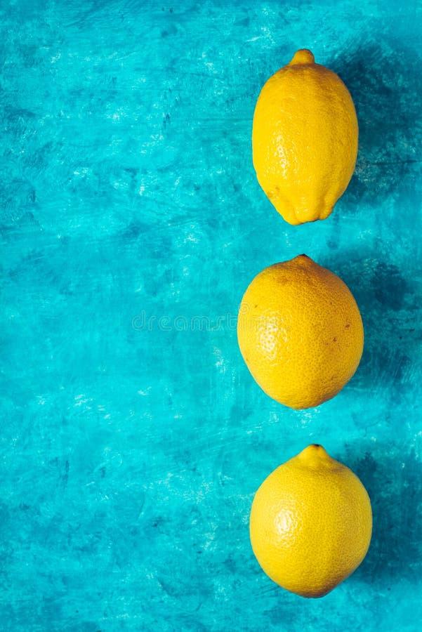 Limoni gialli sulla vista superiore del ciano fondo fotografie stock libere da diritti