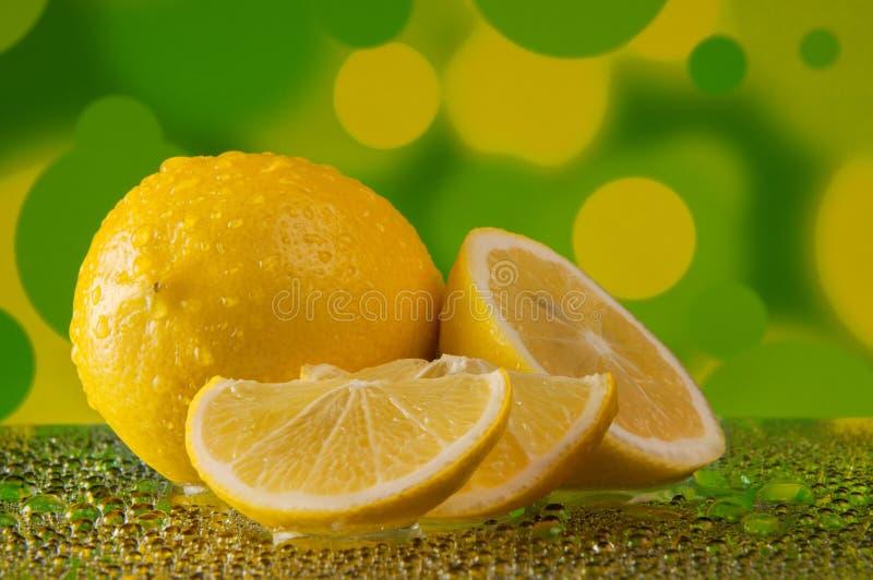 Limoni nelle gocce di acqua sopra su fondo giallo verde chiazzato immagini stock